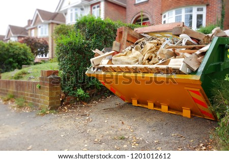 Yellow rubbish skip on driveway. Selective focus on full skip with space to add text in front of bin, footpath & blurry background of green bush fence, houses, brick wall. Renovate, moving concept. Royalty-Free Stock Photo #1201012612