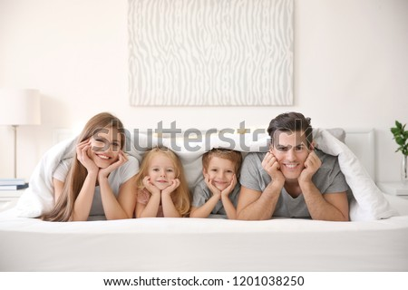 Happy family lying under blanket in bed at home #1201038250