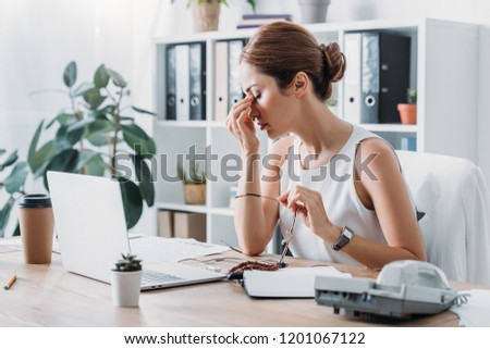 tired businesswoman sitting at workplace with laptop in modern office #1201067122