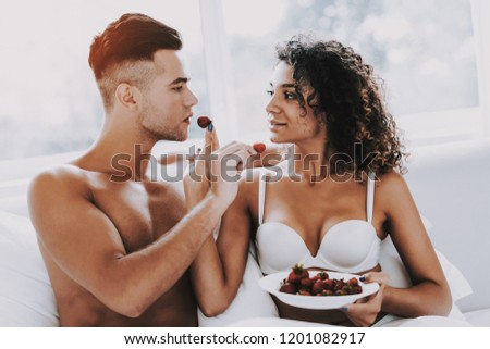 Happy Romantic Couple Eating Strawberrys in Bed. Young Beautiful Couple in Underwear Sitting on Bed with Plate of Fresh Berries. Handsome Man and Attractive Woman in Love. Relationship and Love #1201082917