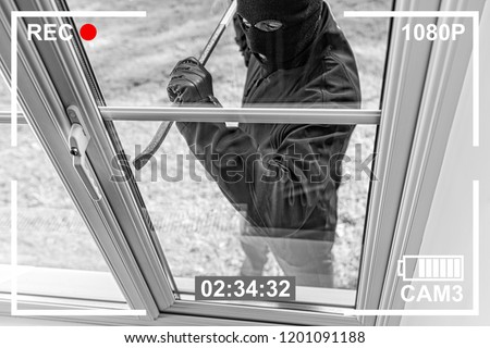 CCTV view of burglar breaking in to home through window with crowbar #1201091188