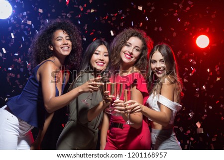 Friends celebrating Christmas or New Year eve with champagne, toasting at camera #1201168957