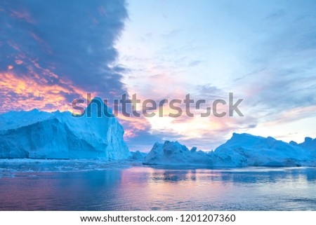 Photogenic and intricate iceberg under an interesting and colorful sky during sunset. Disko bay, Greenland. #1201207360