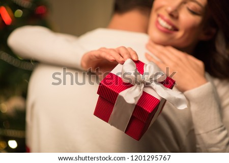 winter holidays and people concept - close up of happy couple with christmas gift hugging at home #1201295767