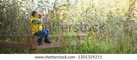 Little boy with binoculars sitting on a wooden fence in the reeds on the lake and exploring the environment warm autumn day. Wide large panorama #1201329211