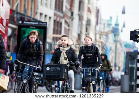 AMSTERDAM, NETHERLANDS- MARCH, 2018: Cyclist in a cold early spring day at the Old Central district of Amsterdam #1201335229