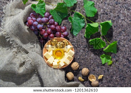 Assortment of cheese with honey, nuts and grape on a rustic cutting board wooden background #1201362610
