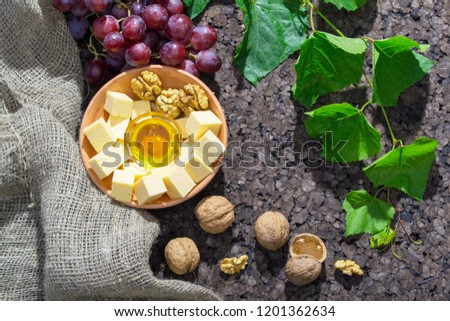 Assortment of cheese with honey, nuts and grape on a rustic cutting board wooden background #1201362634