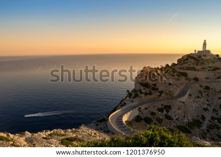 soft dreamy blue warm yellow morning dawn sunrise vertical pic of cap de formentor light house on dry rocky sand cliff & dry grass wavy road with boat on sea ocean background. Mallorca Majorca Spain