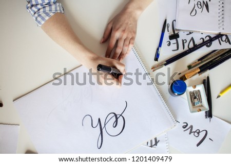 Top view of hand of girl with pen writes on paper with ink #1201409479