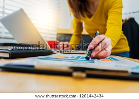 business documents on office desk with laptop and smart phone and graph business diagram and woman working at office. #1201442434