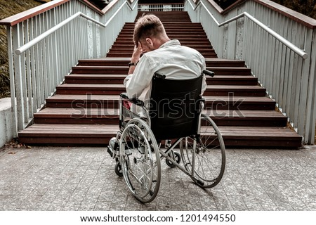 Many stairs. Horizontal image of depressed disabled man sitting in the wheelchair and facing the difficulties with climbing the stairs alone #1201494550