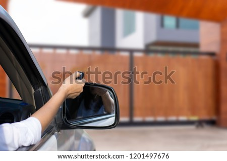 Woman inside car, hand using remote control to open the auto gate when driving and arrive home. Security system and wireless concept. Royalty-Free Stock Photo #1201497676