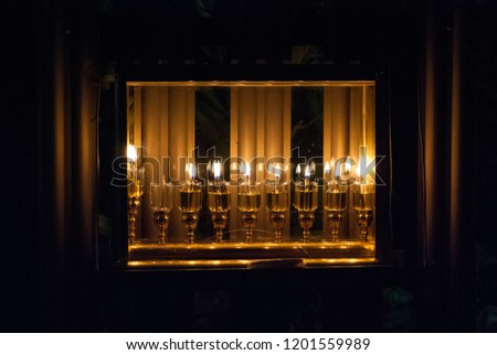 A Jewish tradition in Hanuka holiday is to put the lighted Hanuka's Menorah near the windows and even in glass boxes outdoor as shown in the pictures. Each day we light one more candle up to 8 candles