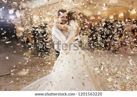 Gorgeous bride and stylish groom dancing under golden confetti at wedding reception. Happy wedding couple performing first dance in restaurant. Romantic moments #1201563220