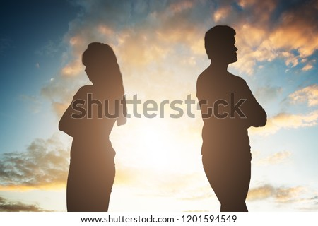Silhouette Of A Unhappy Couple Standing Back To Back Against Cloudy Sky At Sunset #1201594549