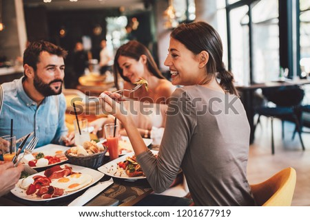 Group of Happy friends having breakfast in the restaurant #1201677919