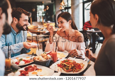 Group of Happy friends having breakfast in the restaurant #1201677937