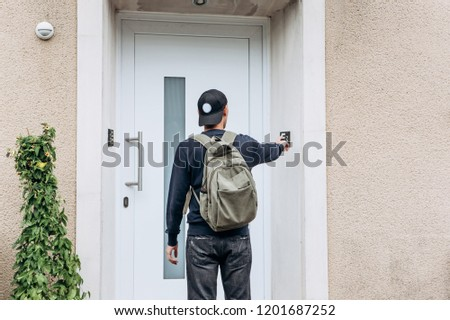 The tourist rings the doorbell to check in to the room he has booked or the student with the backpack returns home after classes at the institute or on vacation. #1201687252