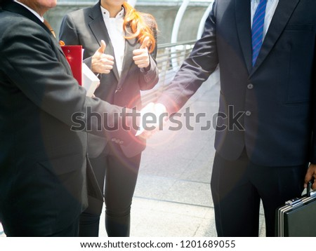 Two businessman stand and handshaking, agreement to become partnership. Success in business meeting. Women in team standing and thumbs up 2 hands. Business concept. #1201689055