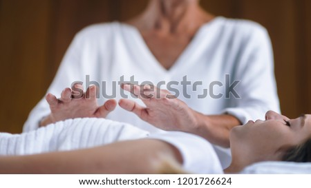 Professional Reiki healer doing Reiki treatment to young woman in health spa center. Healing and balancing heart and crown chakras.  #1201726624
