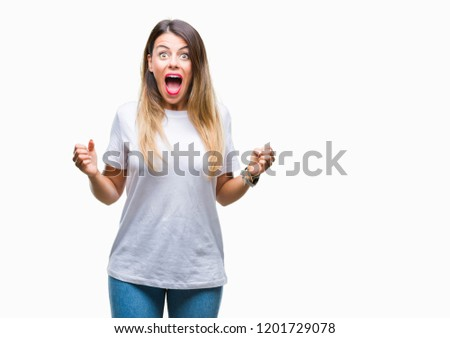 Young beautiful woman casual white t-shirt over isolated background celebrating surprised and amazed for success with arms raised and open eyes. Winner concept. #1201729078