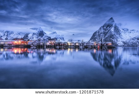 Fishing village with boats at night, Lofoten islands, Norway. Winter landscape with buildings, illumination, snowy mountains, sea, purple cloudy sky reflected in water at dusk. Norwegian rorbuer #1201871578