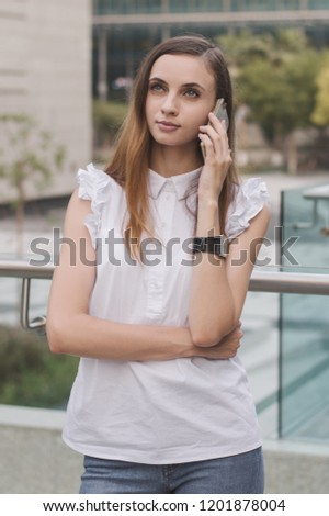 Young european female with brown hair, in white blouse and blue jeans calling via mobile phone with very concentrated and attentive face expression. Communication and mobile phone calls #1201878004