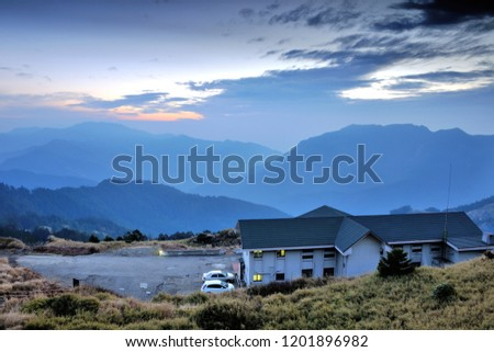 On the high mountains of the continuous mountains, the blue roofs of the white walls of the building, the blue sky has orange clouds. #1201896982