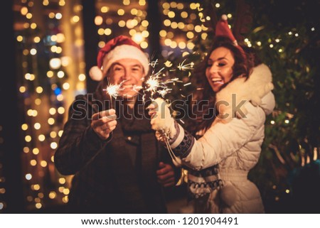 Cute cheerful couple with sparklers enjoying at the Christmas eve in the city street with a lot of holiday's lights. #1201904491