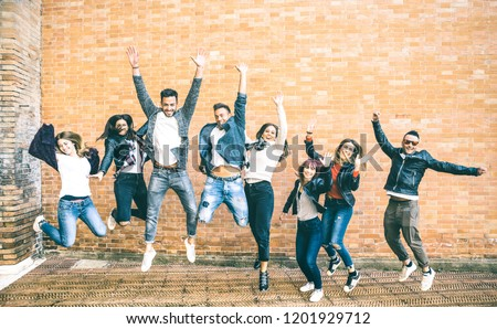 Happy friends millennials jumping and cheering against brick wall in the city - Friendship lifestyle and team concept with young people millenial having fun together - Teal and orange vintage filter #1201929712