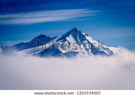 A beautiful mountain peak reaching out of the clouds on a winter day in February. Picture taken in Tignes in the Savoie department in the Rhône-Alpes region in south-eastern France #1201934005