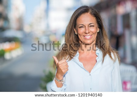 Beautiful middle age hispanic woman at the city street on a sunny day pointing and showing with thumb up to the side with happy face smiling #1201940140