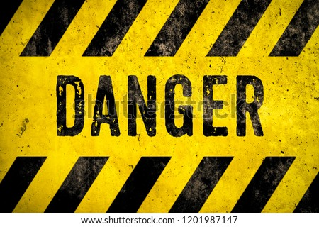 DANGER warning sign word text as stencil with yellow and black stripes painted over concrete wall cement texture background. Concept image for caution, dangerous area and hazard. Royalty-Free Stock Photo #1201987147