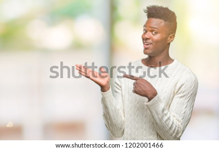 Young african american man over isolated background amazed and smiling to the camera while presenting with hand and pointing with finger. #1202001466