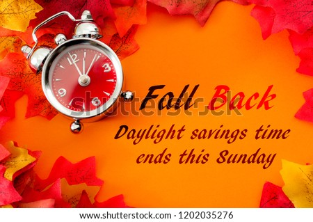 Fall back, the end of daylight savings time and turn clocks back on hour concept with a clock surrounded by dried yellow leaves with the text Fall back, daylight savings time ends this Sunday #1202035276