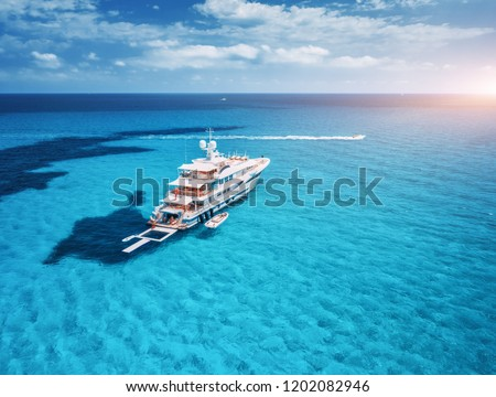 Yacht on the azure seashore in balearic islands. Aerial view of floating boat with people in transparent sea at sunset in summer. Top view from drone. Seascape with luxury yachts in bay. Travel #1202082946