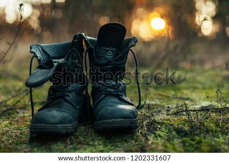 Close up of vintage pair of walking boots on boulder grassland background. Hard travel concept #1202331607