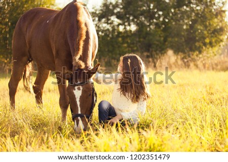 Young girl sitting next to the sorrel horse on the yellow grass #1202351479