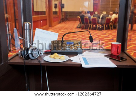 translators cubicle . interpreting - Microphone and switchboard in an simultaneous interpreter booth . Soft focus of wireless Conference microphones and notebook in a meeting room. Royalty-Free Stock Photo #1202364727
