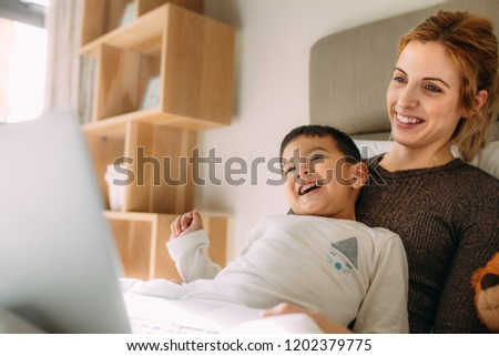 Little boy with mother having great time at home. Smiling woman and son with laptop on bed. #1202379775