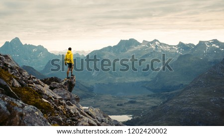Adventurous man is standing on top of the mountain and enjoying the beautiful view during a vibrant sunset. Beautiful Nature Norway natural landscape aerial photography Royalty-Free Stock Photo #1202420002
