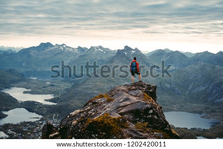 Adventurous man is standing on top of the mountain and enjoying the beautiful view during a vibrant sunset. Beautiful Nature Norway natural landscape aerial photography #1202420011