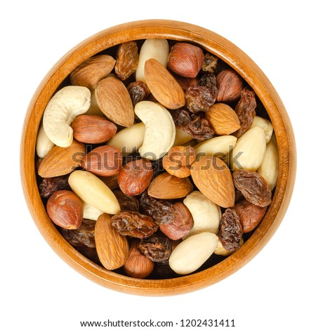 Nuts and raisins in wooden bowl. Snack mix of dried almonds, hazelnuts, cashews and raisins. Trail mix. Edible, raw, organic and vegan. Isolated macro food photo closeup from above on white background #1202431411