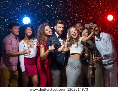 Holiday group selfie. Young friends having fun at New Year's Eve party and taking photo, copy space #1202514973