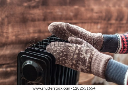Women's hands in Christmas, warm, winter mittens on the heater. Keep warm in the winter, cold evenings. Heating season #1202551654
