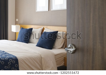 Hotel room , Condominium or apartment doorway with open door in front of bedroom background
