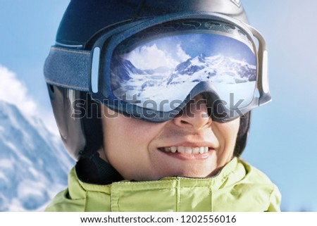 Portrait of man at the ski resort on the background of mountains and blue sky.A mountain range reflected in the ski mask #1202556016
