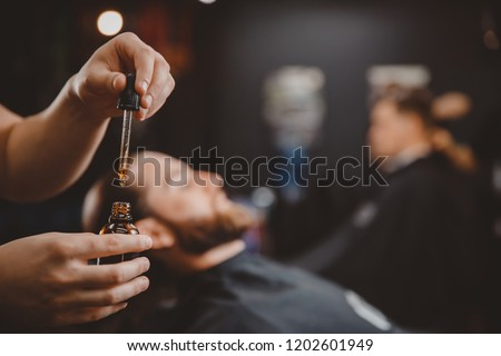 Oil for spa grooming and beard growth for man in a dropper. Concept barbershop. #1202601949