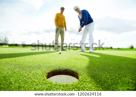 One of two active buddies going to hit golf ball by club while playing at leisure #1202624116